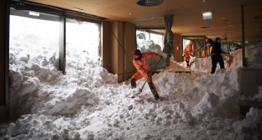 People clear snow from inside the Hotel Saentis in Schwaegalp, Switzerland on Friday after an avalanche swept into the hotel.