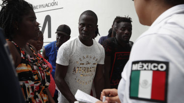 Migrants, mostly from Africa, wait for a ticket to register their entry into Mexico at an immigration station in Tapachula.