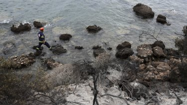 Rescuers search for people in the water along the coastline in Mati, Greece.