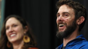 Runner Travis Kauffman, accompanied by his girlfriend Annie Bierbower, answers reporters' questions about his encounter with a mountain lion.