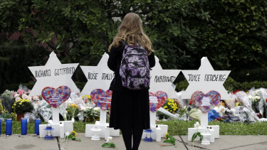A person stands in front of Stars of David that are displayed in front of the Tree of Life Synagogue.