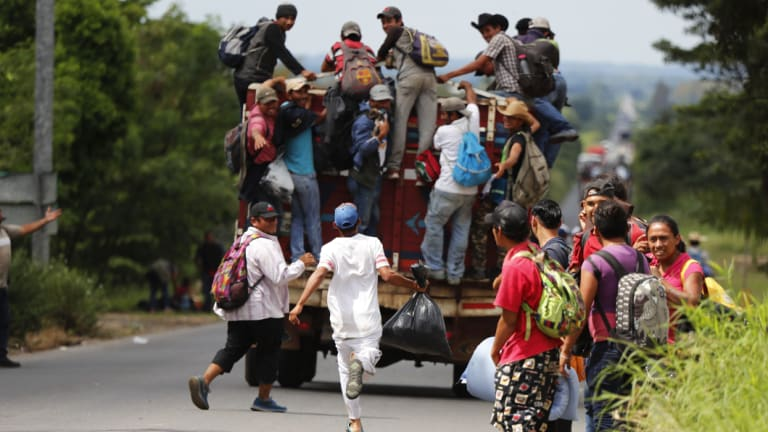 A migrant runs to catch a ride as his fellow Central American migrants, part of the caravan hoping to reach the US border, get a ride.