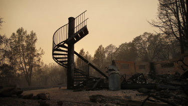A spiral staircase stands in the remains of a burned out home in Paradise, California.