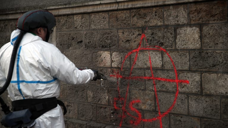 A municipal worker removes graffiti in Paris as monuments reopened, council workers cleaned debris and shop owners tried to put the city back together on Sunday.