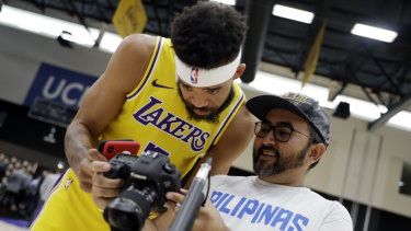 The Lakers' JaVale McGee looks at a photo taken of him at the team's media day.