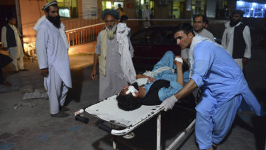 A wounded man is brought by stretcher into a hospital in Jalalabad city, capital of Nangarhar province, east of Kabul, Afghanistan, on Saturday after the bombing.