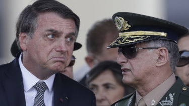 Brazils President Jair Bolsonaro, left, talks with Army Commander General Edson Leal Pujol, during a military ceremony.