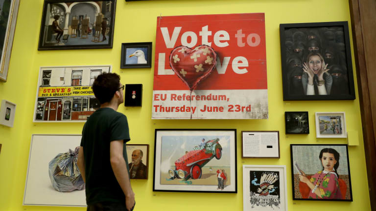 """British artist Banksy's """"Vote to Love"""" message over a UKIP placard is among the works in the Royal Academy of Arts' annual Summer Exhibition."""