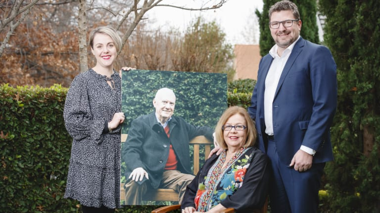 Steve Doszpot's daughter Amy, his widow Maureen and son Adam, with a photo of the late MLA, who has been posthumously awarded a Medal of the Order of Australia.