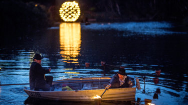 Staff at Compagnie Carabosse light floating fire pots from a paddle boat.