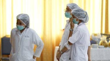 Hospital workers watch a press conference where the rescued boys are being treated.