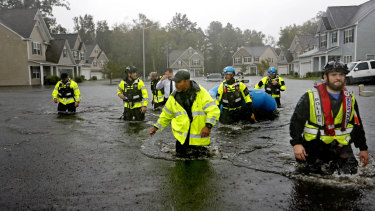 Members of the North Carolina Task Force urban search and rescue team wade through a flooded neighborhood.