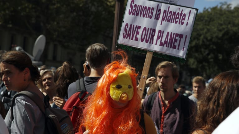 A man holds a poster reading: Save our planet, during a protest in Paris on Saturday.