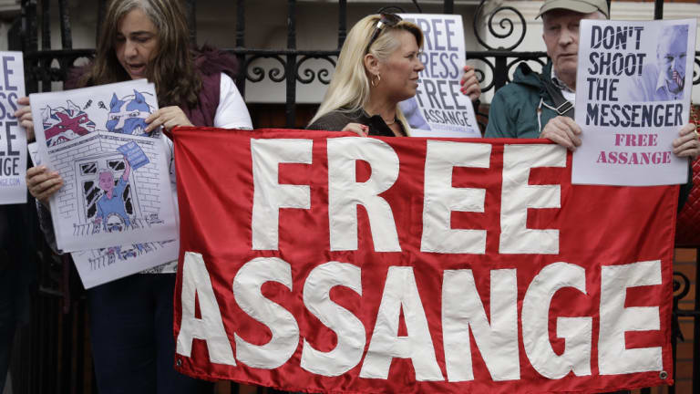Supporters of WikiLeaks founder Julian Assange stand outside of the Ecuadorian embassy as Assange addresses the media, in London.