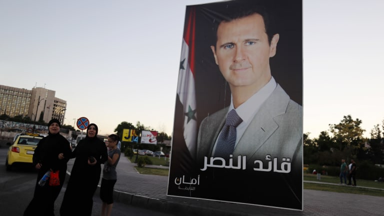 """A poster of President Bashar al-Assad with Arabic that reads, """"Leader of the victory,"""" hangs on a street at Omayyid Square, Syria."""