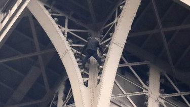 A climber is pictured between two iron columns of the Eiffel Tower.