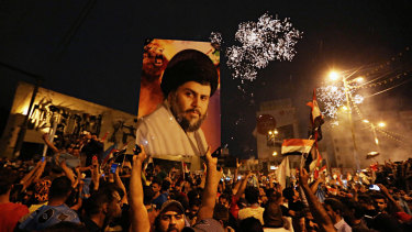 Supporters of Shiite cleric Muqtada al-Sadr carry his image as they celebrate in Tahrir Square, Baghdad, in May.