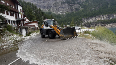 A worker uses a snow shovel to clean the road of the nineteenth stage of the Tour de France.