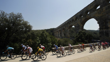 Julian Alaphilippe, wearing the overall leader's yellow jersey, rides with the pack next to the Pont du Gard.