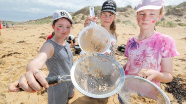 Terang College students Gemma, Abbey and Charlotte collect nurdles on Second Beach, Warrnambool.
