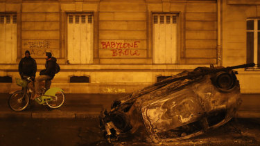 "A burned out car and the slogan, ""Babylon burns"" in Paris on Sunday, local time."
