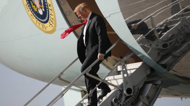 Donald Trump walks down the stairs of Air Force One during his arrival at Palm Beach International Airport.
