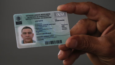 A Honduran migrant shows his temporary Mexican humanitarian visa at the border between Mexico and Guatemala, where many migrants are waiting for humanitarian visa applications to be processed.