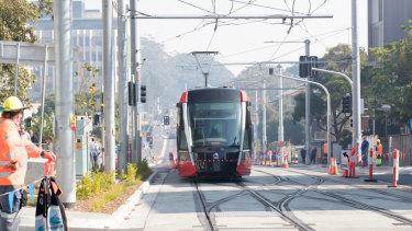 A tram rolls along High Street at Randwick.