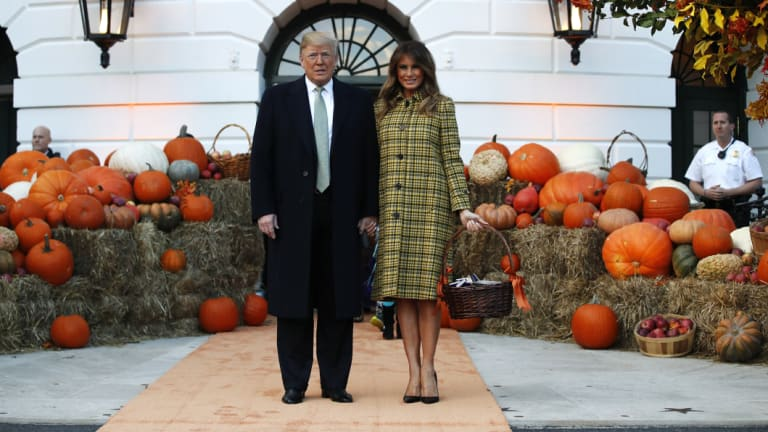 President Donald Trump and first lady Melania Trump hold hands after arriving for a Halloween trick-or-treat event at the White House.