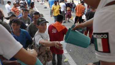 Central American migrants eat lunch, courtesy of Mexican officials, on the border bridge between Mexico and Guatemala.