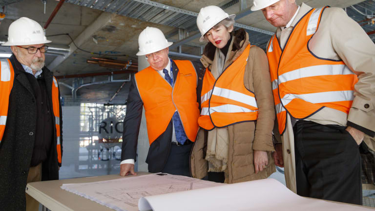 ANU vice-chancellor Brian Schmidt (centre left) and philanthropists Louise and Graham Tuckwell (right) view the plans for Wright Hall, a student residence set to open next year.