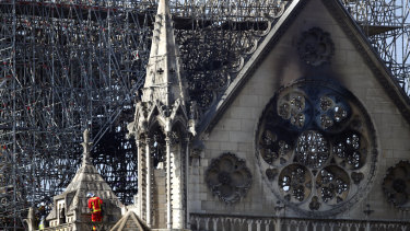 A firefighter makes his way on a balcony of Notre-Dame Cathedral.