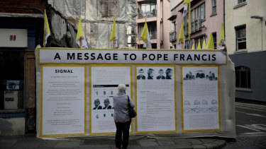 A passerby looks at an art installation by Mannix Flynn protesting the Pope's visit in Dublin, Ireland.