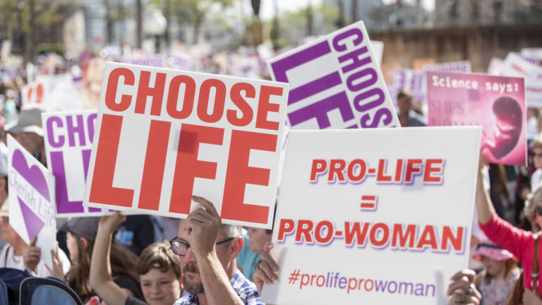Protesters hold placards during a pro-life rally in Brisbane on Saturday.