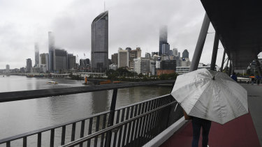 A woman crosses the Goodwill Bridge on a rainy afternoon in Brisbane on Friday, August 7.