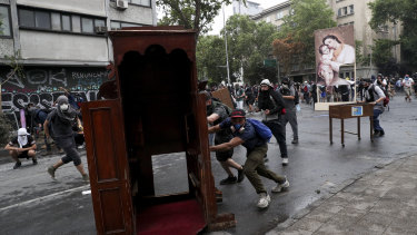 Anti-government protesters drag items from a church to be added to a barricade in Santiago, Chile.