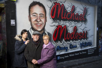 Much loved: Gisella Hardy, left, and her parents Marcello and Gail at the Hosier Lane mural of their brother and son, Michael Modesti, who has been missing for two years.