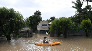 A local resident pedals his kayak through flooded streets in Rockhampton, during the aftermath of Cyclone Debbie.