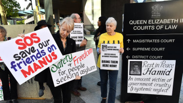 Protester Jillian Oldfield (left) from the Refugee Action Collective is seen during a vigil for deceased asylum seeker Hamid Khazaei outside the Brisbane Magistrates Court.