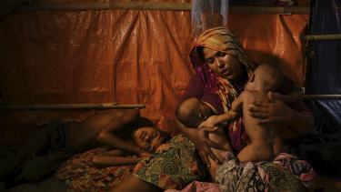 Rohingya woman Fatima Begum comforts her twins Asia and Rubina as her sick son Sadeka lays by her side at the Balukhali camp in Bangladesh.