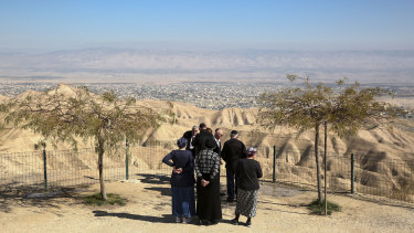 Jewish settlers stand at a view point overlooking the West Bank city of Jericho which will be left almost an island if Israel annexes the Jordan Valley as planned.