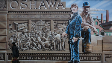 A pedestrian walks past a mural depicting workers in Oshawa, Ontario, Canada. After churning out cars and trucks for General Motors for more than a century, the town could find itself without a car plant.