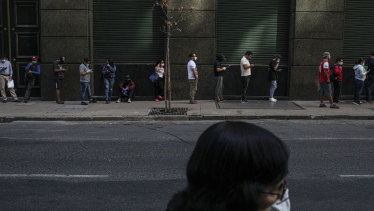 Not just about the money: people wait in line to collect unemployment insurance in Santiago.
