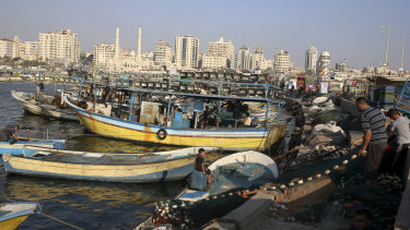 Palestinian fishermen repair their nets in Gaza City. On Tuesday Israel said it was tightening its naval blockade to limit Palestinians from sailing beyond three nautical miles off Gaza's coast, from six nautical miles previously.