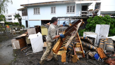 A man helps strangers remove flood-damaged items from their home in the suburb of Rosslea in Townsville on Thursday.