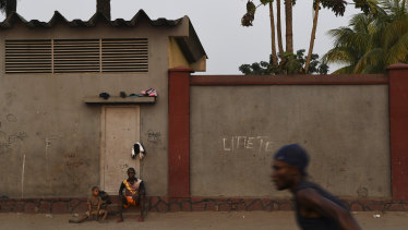 A man and a boy watch a game of soccer on the streets of the Democratic Republic of Congo's capital Kinshasa.