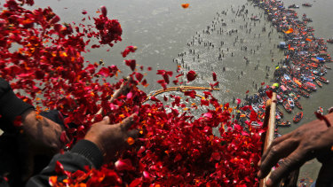 Government officials throw flowers from a helicopter onto thousands of Hindu devotees in the water at Sangam, the confluence of three sacred rivers - the Yamuna, the Ganges and the mythical Saraswati.