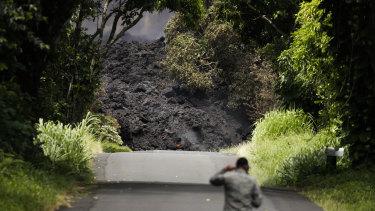 US Air Force Lieutenant Colonel Chuck Anthony walks towards a wall of lava entering the ocean near Pahoa, Hawaii on Sunday,