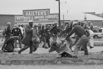 A state trooper swings a billy club at John Lewis, right foreground, chairman of the Student Nonviolent Coordinating Committee, to break up a civil rights voting march in Selma, Alabama, in 1965.