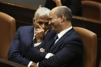 Israel's new Prime Minister Naftali Bennett, right, sits with Yair Lapid during a Knesset vote to oust Netanyahu. Bennett will serve for the first two years and Lapid for the next two of the unity government's term.